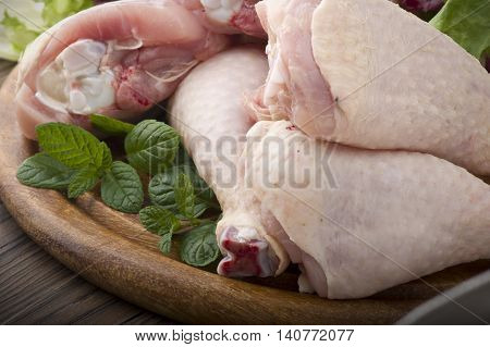 Fresh skinless chicken thighs and legs on cutting board poster