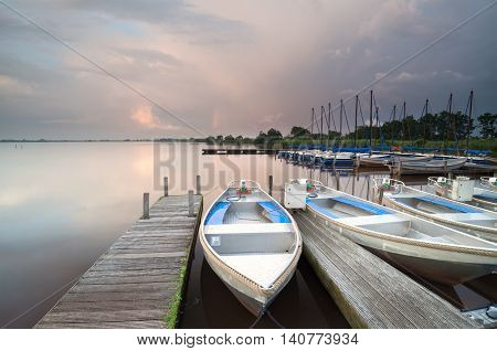 boats and yacht by pier on big lake Netherlands