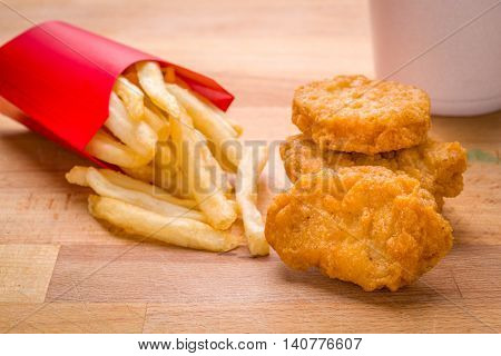 Kids Child meal Golden brown Chicken nuggets and French fries on a wood background
