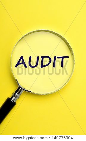 The word Audit on yellow background closeup