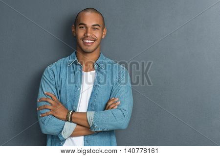Portrait of handsome man standing with arms crossed in smart casual clothing against a grey wall. Smiling young african guy looking at camera leaning on grey background with copy space.