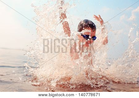 kid dives into the water. splashes of water around a swimmer diving into the water. kid excited about swimming. the concept of a happy childhood