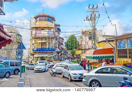 HAIFA ISRAEL - FEBRUARY 20 2016: The narrow street of Arab Market in Wadi Nisnas neighborhood is full of fruit and vegetable stalls and parked cars on February 20 in Haifa.