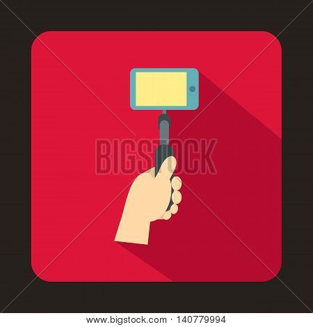 Hand holding a selfie stick with mobile phone icon in flat style with long shadow. Device symbol