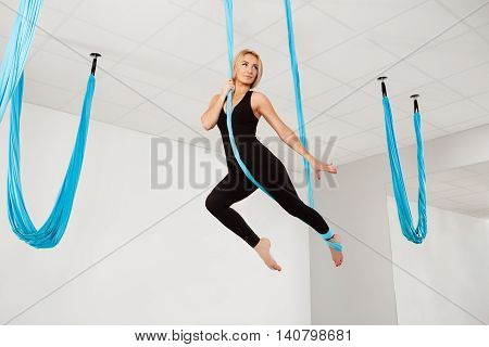 Young beautiful blonde girl miling, practicing aerial yoga in gym.