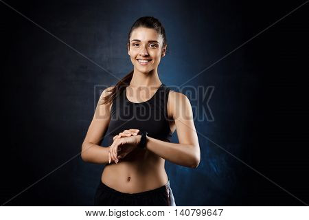 Young beautiful brunette sportive girl posing over dark background. Copy space.