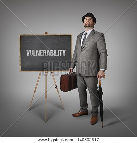 Vulnerability text on  blackboard with businessman holding umbrella and suitcase