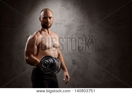 Young powerful sportsman training with dumbbells, looking at camera over dark background. Copy space.