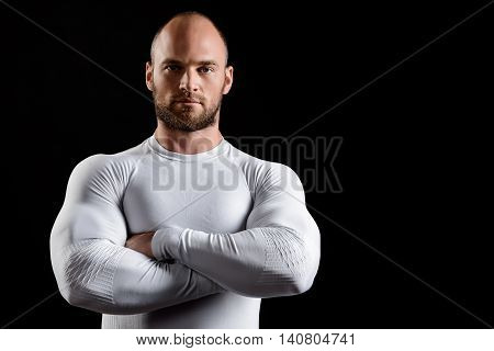 Young powerful sportsman in white clothing looking at camera, arms crossed over black background. Copy space.