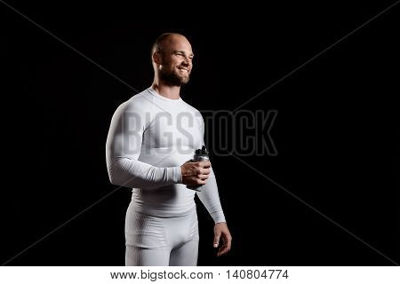 Young powerful sportsman in white clothing smiling, holding bottle over black background. Copy space.