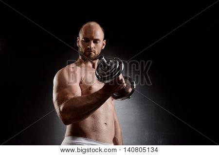 Young powerful sportsman training with dumbbells over black background. Copy space.