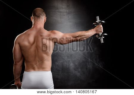 Young powerful sportsman training with dumbbells, standing back to camera over black background. Copy space.