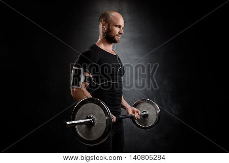 Young powerful sportsman in heaphones training with barbell over black background. Copy space.