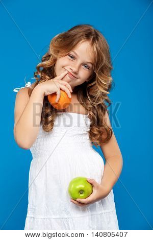 Young pretty girl holding apple and orange, smiling, looking at camera over blue background.