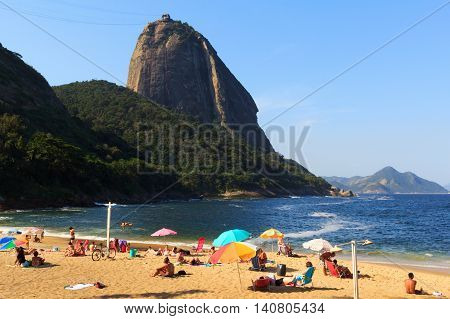 RIO DE JANEIRO - August 7: Tourists laying in the sun on beach Praia Vermelha with view to Sugarloaf on August 7 2015 in Rio de Janeiro.