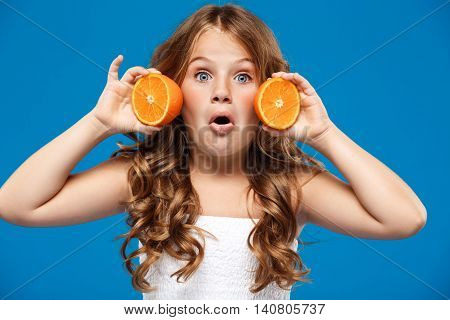 Surprised young pretty girl holding oranges, looking at camera over blue background.