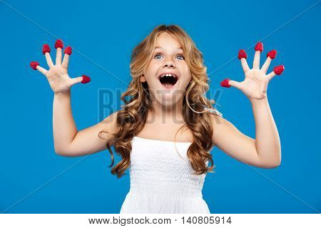 Surprised young pretty girl holding raspberry smiling over blue background.