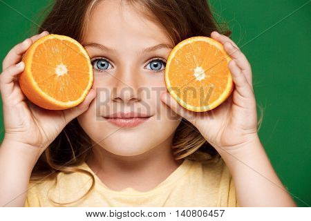 Young pretty girl holding orange, looking at camera, smiling over green background.