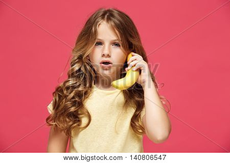 Young pretty girl holding banana like phone, looking at camera over pink background. Copy space.