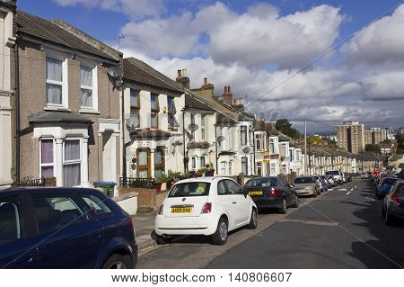 LONDON, UNITED KINGDOM - SEMPTEMBER 12 2015: Row of traditional British houses in a street in the suburbs of London with car parked on the street