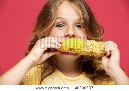 Young pretty girl eating corn, looking at camera over pink background.