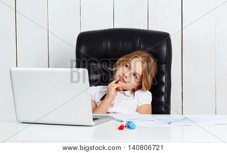 Young beautiful girl sitting at working place, thinking in office.