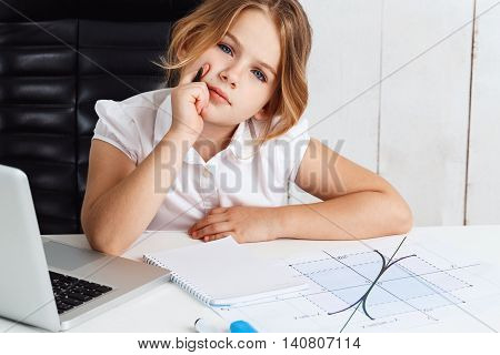 Young beautiful girl sitting at working place, thinking, looking to camera in office.