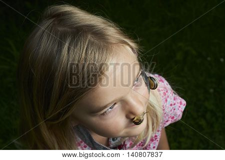 Portrait of cute blond child girl with snail on her face