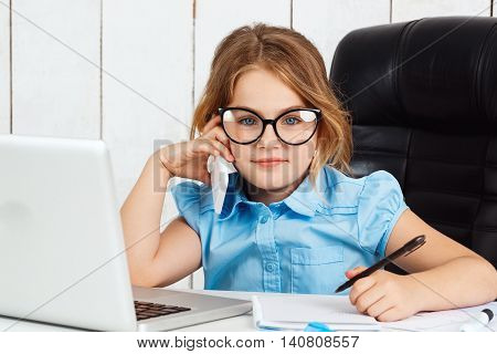 Young beautiful girl in glasses speaking phone at working place, looking to camera, smiling in office.