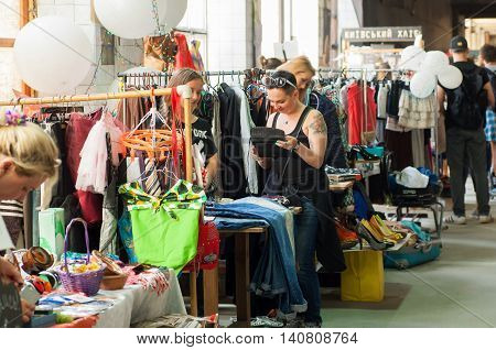 KYIV, UKRAINE - JUL 23, 2016: Women shopping inside the huge hall of market of vintage clothes on July 23, 2016. Kiev is the 8th most populous city in Europe.