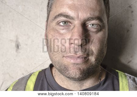 A stressed man. emotion portrait worker in front of a concrete wall