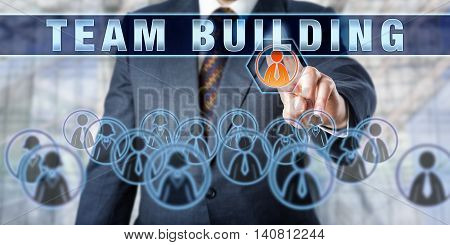 Corporate manager is pressing TEAM BUILDING on a virtual control monitor. Business concept for managing team-based working relationships and the impact of globalization trends on virtual workplaces.