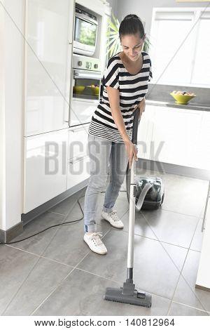 Homehelp vacuuming kitchen floor