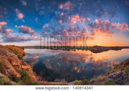Beautiful panoramic landscape with colorful cloudy sky lake and mountains. Summer sunset at the river with clouds reflected in water. Panorama. Nature background