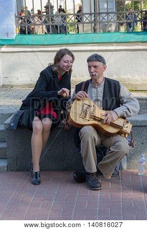 Kiev Ukraine - May 1 2016: Girl with a street musician playing instrument nastarinom - ogranistrume