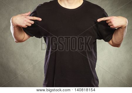 Fashionable casual man in black blank shirt with empty copy space pointing at himself. Guy in studio on black. Fashion advertisement.