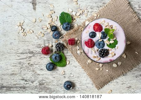 fruit yogurt with berries in a glass on wooden background. healthy breakfast. top view
