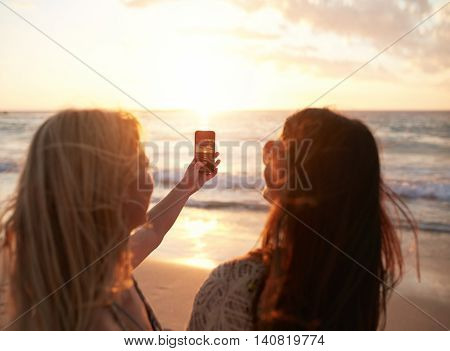 Female Friends On The Beach Photographing Sunset