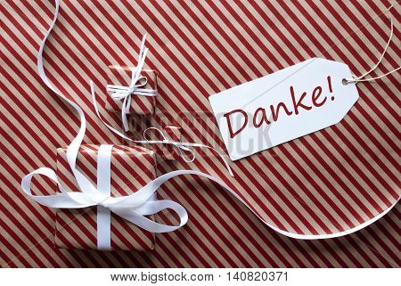 Two Gifts Or Presents With White Ribbon. Red And Brown Striped Wrapping Paper. Christmas Or Greeting Card. Label With German Text Danke Means Thank You