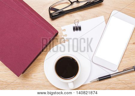 Top view of wooden office desktop with blank white smartphone coffee cup closed red book glasses paper sheet peg and pen. Mock up