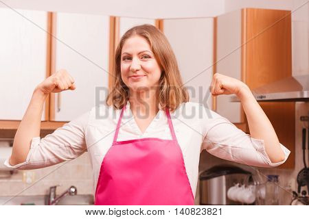 Happy successful and cheerful woman wearing pink apron. Smiling housewife making winning fists hands up gesture in kitchen. Positive emotion.