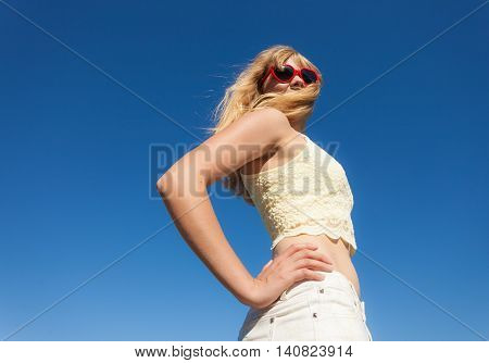 Summer happiness and lifestyle concept. Lovely blonde girl in sunglasses relaxing outdoor against blue sky wide angle unusual view