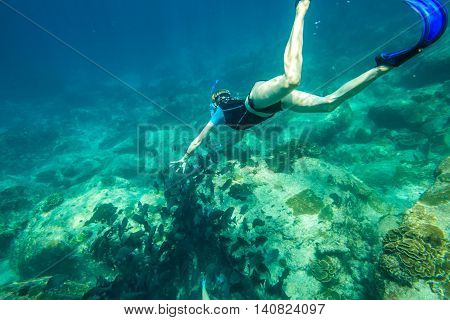 Young woman free diving in the blue waters of the popular Similan Islands in Thailand, one of the tourist attraction of the Andaman Sea. On background a lot of fish.