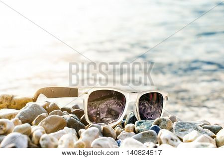 Black mirrored sun glasses on a stones. Shadow from glasses. Sunlight. Summer concept.