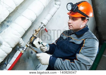 Plumber technician works with water meter