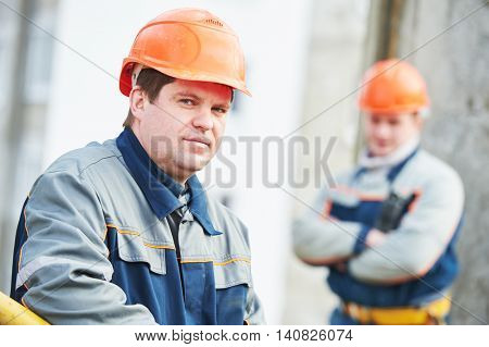 Portrait of two workers at construction site