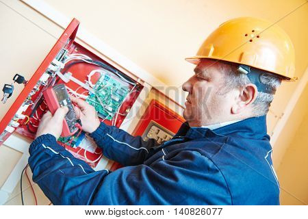 electrician measuring electric circuit with multimeter in fuse box