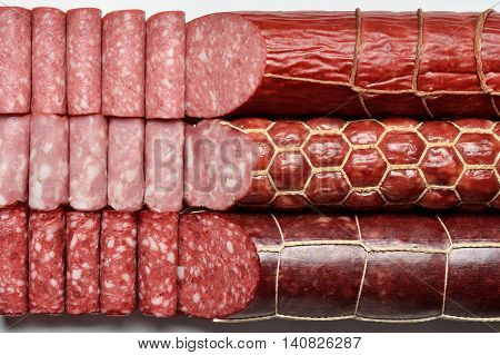 Three types of smoked sausages sticks and slices