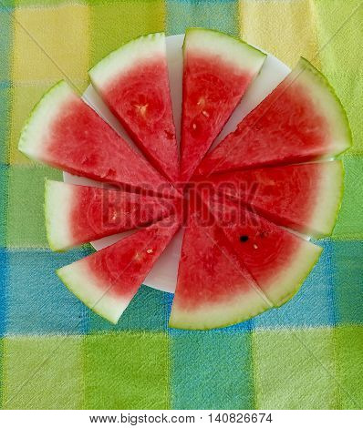 Organic seasonal summer watermelon sliced on tablecloth
