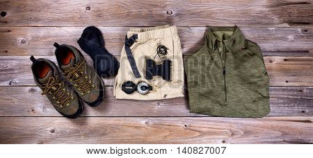 Top view of hiking gear to include hiking shoes shorts shirt compass socks and binoculars on rustic wooden boards